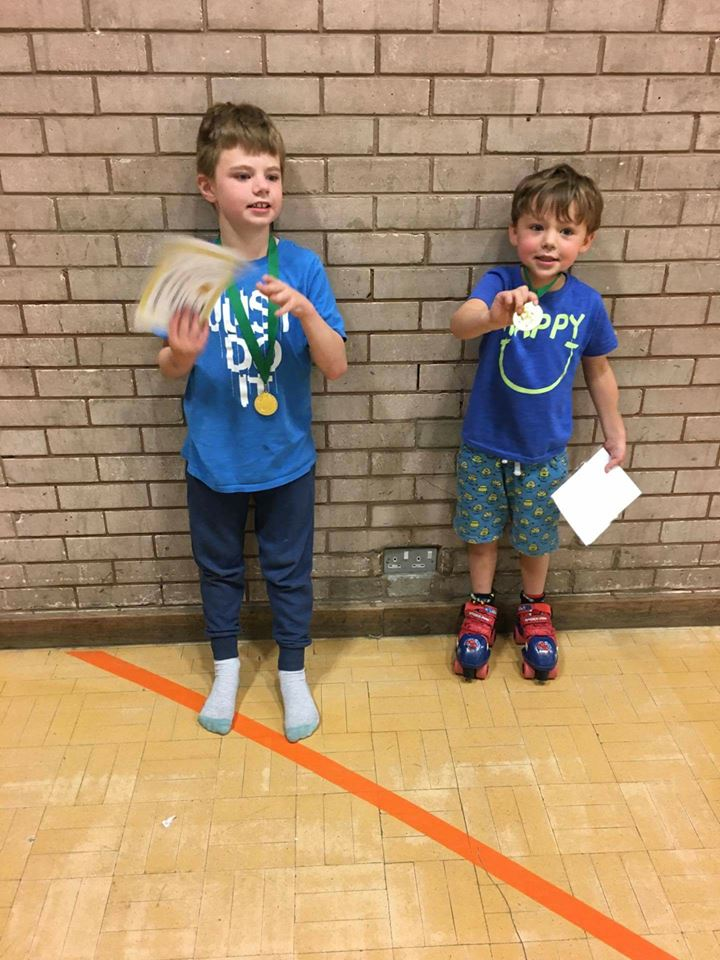 Two boys are holding up their medals and certificates to the camera